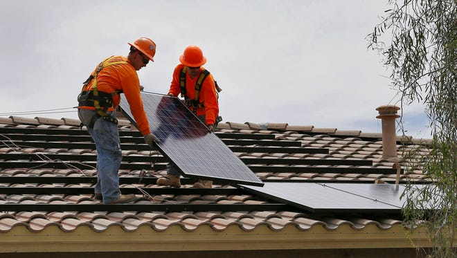 Adam Hall, right, and Steven Gabert install solar panels on a roof for Arizona Public Service on July 28 in Goodyear, Ariz. In this July 28, 2015, photo.