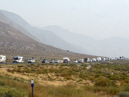 A long line of cars, trucks and RVs snakes around a