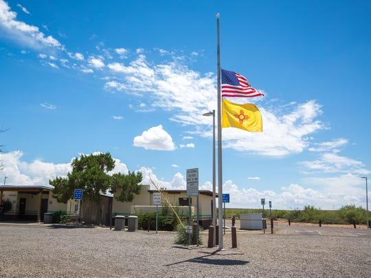 The U.S. and New Mexico flags fly at half-staff, Saturday, August 13, at the rest stop near Radium Springs where a man was shot while being carjacked on Friday.
