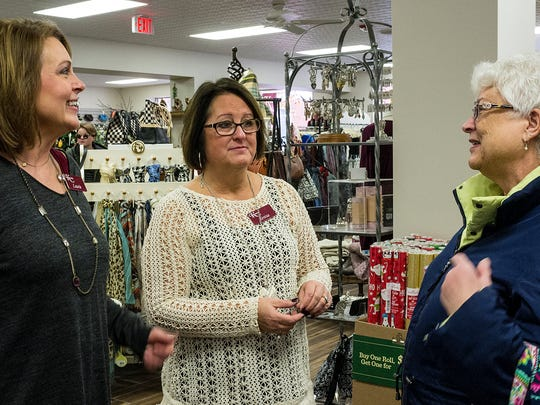Kean's store manager Laurie Reed, left, and store owner Teresa Wren, talk with longtime customer Tonya Maj on Saturday about the re-opening of the store.