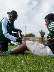 Cass Tech football player, Zaire Faulkner, 17, gets taped by Coach Blakely before the start of practice on Sept. 27, 2016.