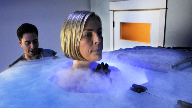 Ventura resident Dawn Proctor stands inside a cryosauna while CryoWorks owner JB Drake monitors the controls. Proctor suffers from nerve disorders, chronic pain and inflammation and says cryotherapy has helped.