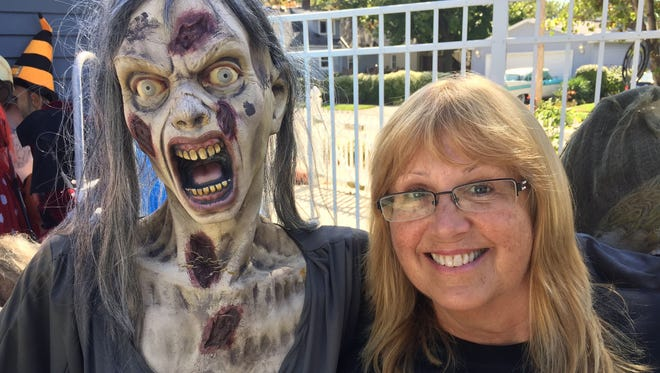 Sally Omally Schroeder, 60, of Berkley, poses with one creature she saved from her massive monster garage sale on Thursday, Sept. 24, 2015.