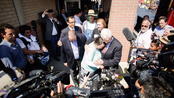 Kim Davis hugs her attorney, Matt Staver, with Mike Huckabee to the left, after be released, Tuesday.