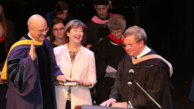 President Robert Clark (left) is sworn in with Ruth Ann Clark and Wesley Board of Trustee Chair Robert V.A. Harra, Jr.