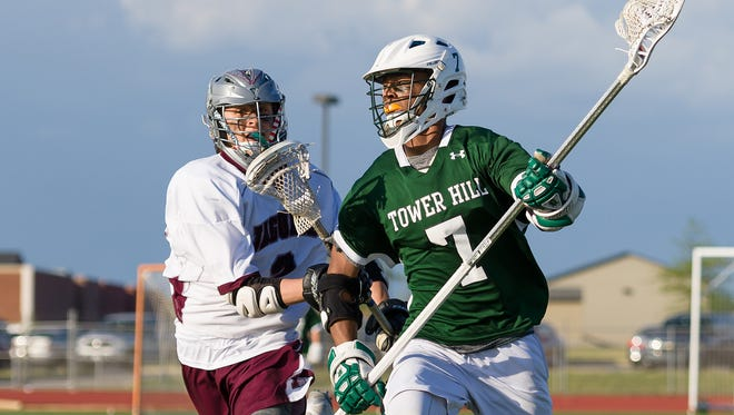 Kevin Turner (7) of Tower Hill carries the ball past Logan Yoder of Appoquinimink during the Hillers' win on April 26. Tower Hill moved up to No. 2 in the boys lacrosse rankings this week.