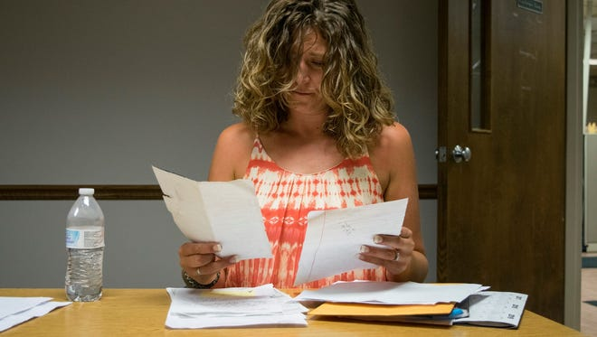 Nicole Higgins looks through documents and records relating to her husband, Kevin Higgins.  Nicole doesn't blame the officers that killed Higgins as he left the Union Avenue Tap on July 17, but she is wondering why he wasn't able to get proper care for his military-related mental illness.