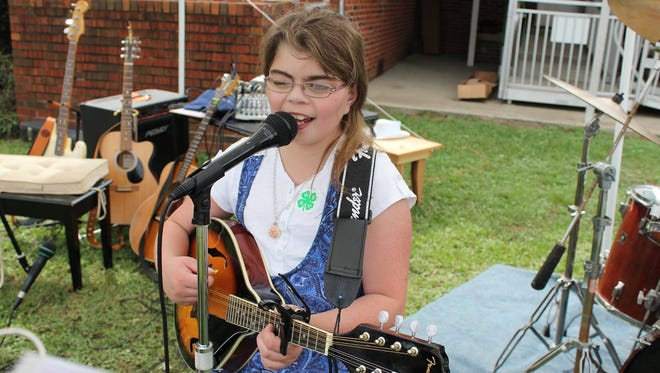 Ashley Allen playing the mandolin at an event.