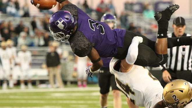 Justin Fulks of USF dives over Wes Bednar of SMSU for a touchdown during Saturday night's game at Bob Young Field.