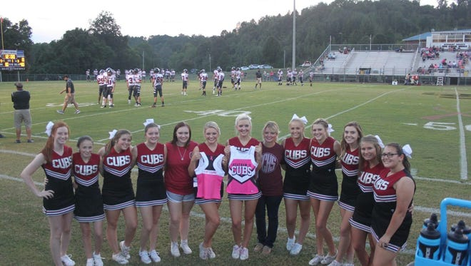"""The Cheatham County Central High cheer squad. The cheerleaders wear special pink uniforms reading """"For Leanne"""" on the back in memory of their former coach Leanne Pulley, who died of breast cancer last year. At center, holding the front-facing top, is Pulley's daughter Sarah."""