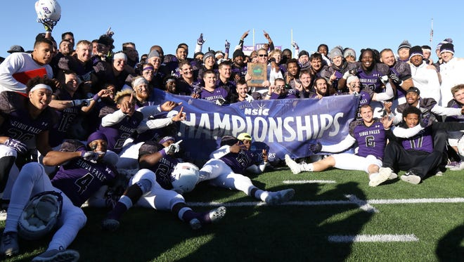 Members of the USF football team pose for a photo after defeating Wayne State and finishing 11-0 to capture the NSIC Championship on Saturday at Bob Young Field.