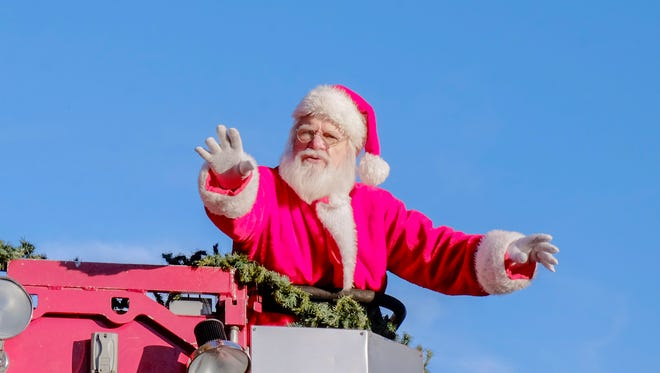 Santa Claus waved to everyone as he sat atop a fire truck.