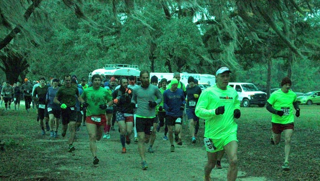 Partcipants run in the Swamp Forest Trail races Saturday.