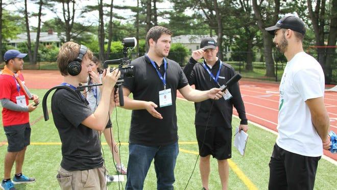 Craig Gorbunoff (center, holding microphone) interviews Jets wide receiver Eric Decker.