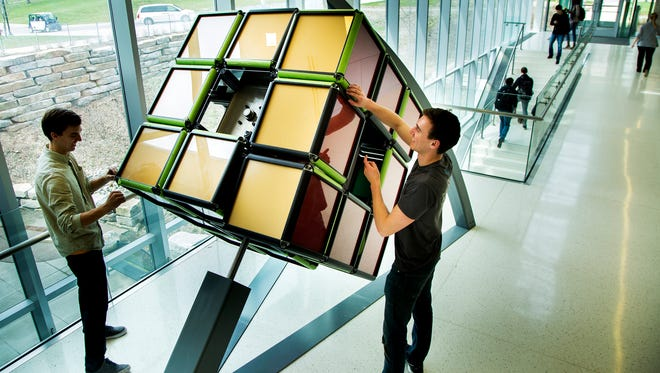 Jason Hoving and Ryan Kuhn install a giant rubik's cube into the lobby of the GG Brown Addition on North Campus of the University of Michigan in Ann Arbor on April 10, 2017.