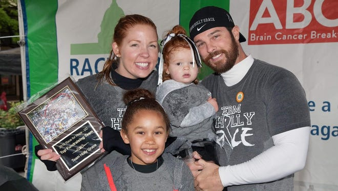 Matt and Holly Gibbons, pictured with two of their three children, are raising money to fight brain cancer.