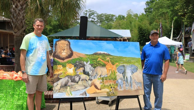 Local artist Gary Delancey, right, recently donated an original painting to the Hattiesburg Zoo.
