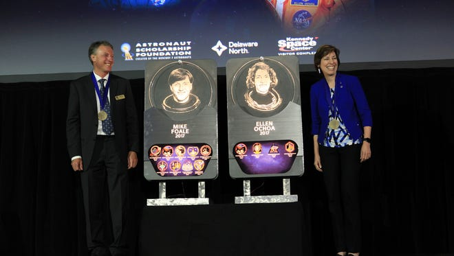 At the space shuttle Atlantis exhibit on Friday at NASA's Kennedy Space Center Visitor Complex, astronauts Michael Foale, left, and Ellen Ochoa, pose with their plaques after being inducted into the U.S. Astronaut Hall of Fame.