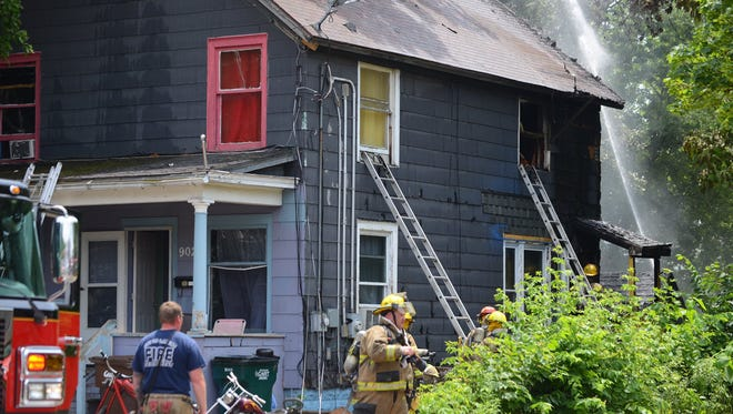 Firefighters work on a duplex fire Tuesday, June 13, 2017, on Kalamazoo Street in Lansing.