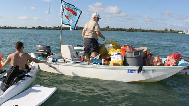 A volunteer with Marine Cleanup Initiative Inc. helps transfer trash collected underwater by volunteer divers to a larger vessel during a past cleanup dive at Fort Pierce Inlet.