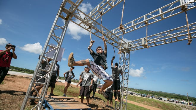 A competitor swings his way through one of the obstacles in Trench Challenge 2016 at the Guam International Raceway.  Hundreds of athletes and non-athletes alike enjoyed a rough, dusty, muddy day in the sun.