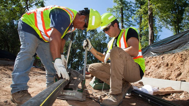 Workers install gas mains.