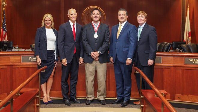 Lucky Goat Coffee owner Ben Pautsch receives Governor's Business Ambassador Award from Gov. Rick Scott.