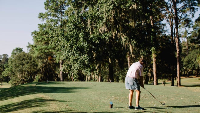 A golfer tees off at Capital City Country Club.