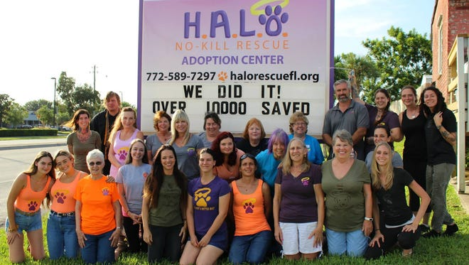 Founder Jacque Petrone,(fifth from left in front row), volunteers and staff celebrating the milestone of saving 10,000 animal lives.
