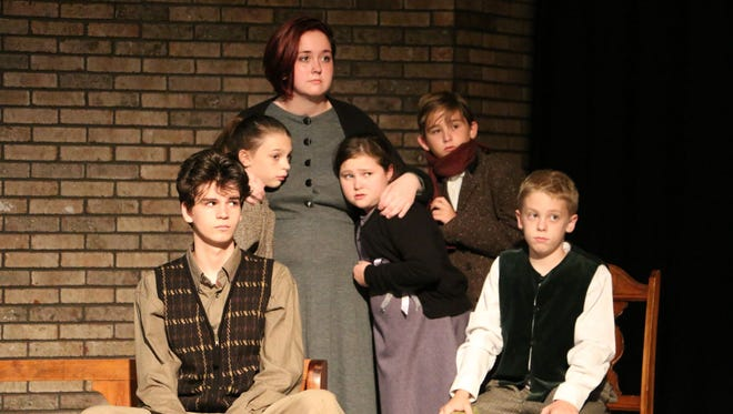 """Frightened children huddle around their mother in a CCS performance of """"Number the Stars."""""""