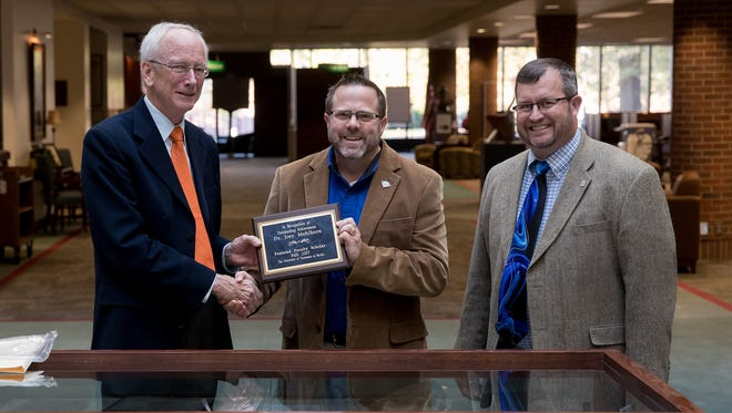Dr. Joey Mehlhorn, chair holder for the Gil Parker Chair of Excellence in Agriculture and Natural Resources, is recognized as the Featured Faculty Scholar for the 2017 fall semester. A reception was held in his honor Nov. 16 in the Paul Meek Library. Presenting the plaque is Dr. Rich Helgeson, interim provost, and joining Helgeson and Mehlhorn for the presentation is Dr. Todd Winters, dean, College of Agriculture and Applied Sciences.