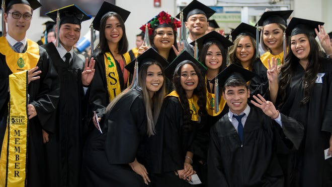 University of Guam Fanuchånan (Fall) 2017 graduates show their Triton Tridents before the Commencement Ceremony at the UOG Calvo Field House on Sunday, Dec. 17, 2017.