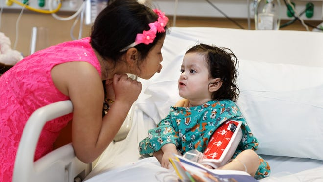 Isabella Soto, right, enjoys a visit from her sister,Danara, 6. Isabella is recuperating after doctors at Johns Hopkins All Children's Hospital in St. Petersburg removed a button battery from Isabella's esophagus. The battery caused damage that will require more surgeries.