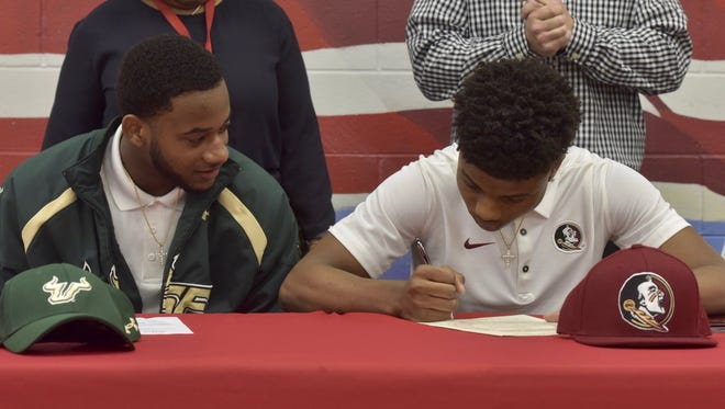 West Florida High defensive back and USF signee Keyon Helton, left, watches twin brother Keyshawn Helton sign with Florida State on Saturday at West Florida High.
