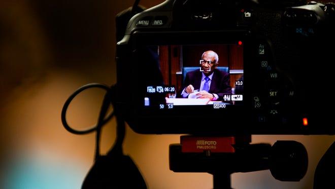 MSU Trustee Joel Ferguson seen through the camera viewfinder of a reporter.
