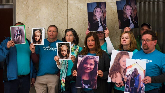 Parents of Larry Nassar victims hold up photos of their daughters from roughly the age they were when they were first assaulted.