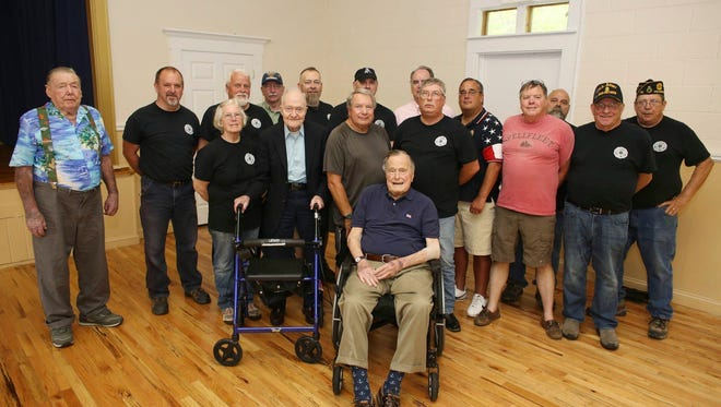 This photo provided by the office of former President George H.W. Bush, shows Bush posing with veterans during  the monthly pancake breakfast at the American Legion Post 159 in Kennebunkport, Maine, on May 26, 2018.