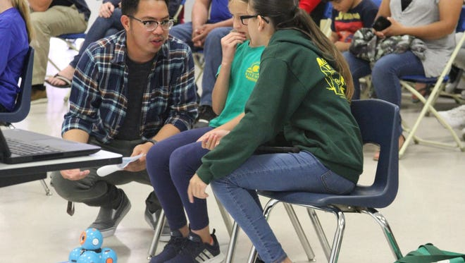 Raymond Ibay, one of the coordinators of the District Robotics Competition, answers questions from Emilie Ritchen School students, Isabella Wedemeyer and Vivienne Nuñez.