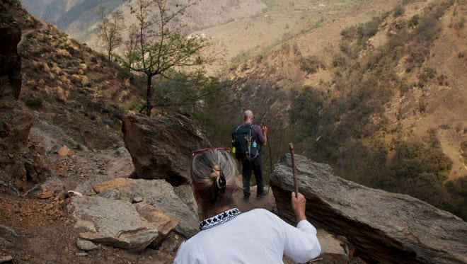 In this March 26, 2017 photo, Elizabeth Brenner, wearing white, and her partner Barry Knight hike through a rocky trail on their way to the spot where Brenner's son, a University of Iowa student, slipped and fell more than 300 feet down a steep gorge in 2011 in the mountains of north India. Hundreds of thousands of American students study abroad each year, but no one can say exactly how many are injured or die.