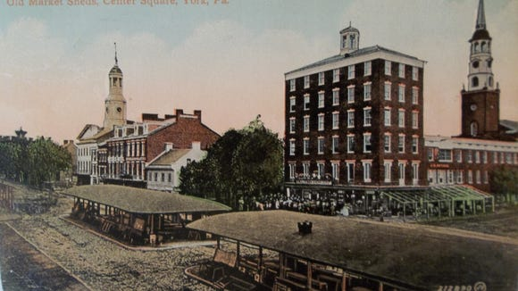 The steeple of Christ Lutheran Church (right) on S. George Street towers over the Hartman store at the corner intersection with Market Street in this colorized postcard of an 1863 photograph of the square and market sheds (Author's postcard collection)