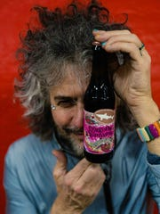 Wayne Coyne of The Flaming Lips greets his new friend, a collaborative beer with Dogfish Head.