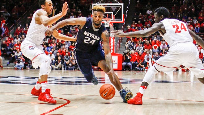 Nevada's Jordan Caroline splits New Mexico's defense of Elijah Brown, left, and Damien Jefferson during the Wolf Pack's 105-104 win over New Mexico.