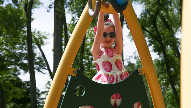 Iris Helfner, 6, plays on the playground at Perinton Park. Iris survived Ebstein's Anomaly, a rare heart defect.