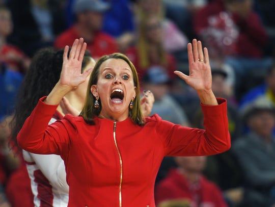 USD's coach Dawn Plitzuweit talks to her team during