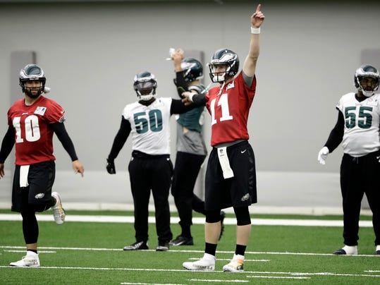 "In this Wednesday, Nov. 30, 2016, photo, Philadelphia Eagles quarterback Carson Wentz (11) and quarterback Chase Daniel (10) warmup during practice at the team's NFL football training facility in Philadelphia. NFL players get to show off their creativity, custom cleats and causes this weekend. The league's ""My Cleats, My Cause"" campaign features more than 500 players wearing colorful cleats to spotlight various causes. (AP Photo/Matt Rourke)"