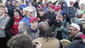 A teen stands in front of a Native American singing and playing a drum at a rally in Washington.