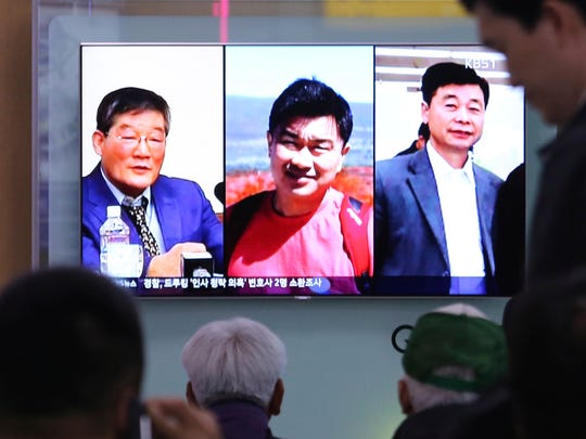 People watch a TV news report on screen, showing portraits of three Americans, Kim Dong Chul, left, Tony Kim and Kim Hak Song, right, detained in the North Korea at the Seoul Railway Station in Seoul, South Korea,  May 3, 2018.