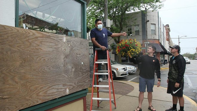 Jayme Santa Cruz, left, hands a plant to Jack Heimer, center, as Jayden Middlesteadt looks on as the three work to board up broken windows at Deininger Floral on Monday in downtown Freeport.