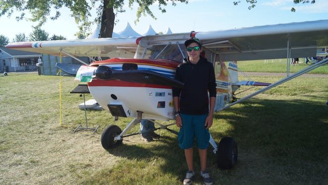 Fourteen-year-old Anthony Akey stands stands next to the Dakota Hawk aircraft, at EAA AirVenture  in Oshkosh. He painted the plane for the HAWK Aviators club based in Colorado and helped fly it back Sunday morning.