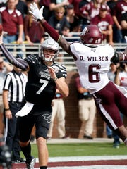 Mississippi State quarterback Nick Fitzgerald (7) throws past the defense of Texas A&M defensive back Donovan Wilson (6) during the second half of their NCAA college football game in Starkville, Miss., Saturday, Nov. 5, 2016. Mississippi State won 35-28. (AP Photo/Rogelio V. Solis)